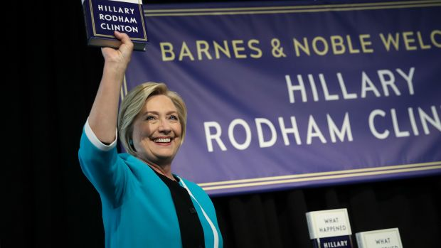 Former U.S. Secretary of State Hillary Clinton holds up a copy of her new book What Happened at a book signing event at a Barnes and Noble bookstore on September 12th, 2017, in New York City.