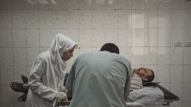A doctor and nurse stitch a man's finger in Al-Shifa Hospital, one of the largest medical complexes in the Gaza Strip.