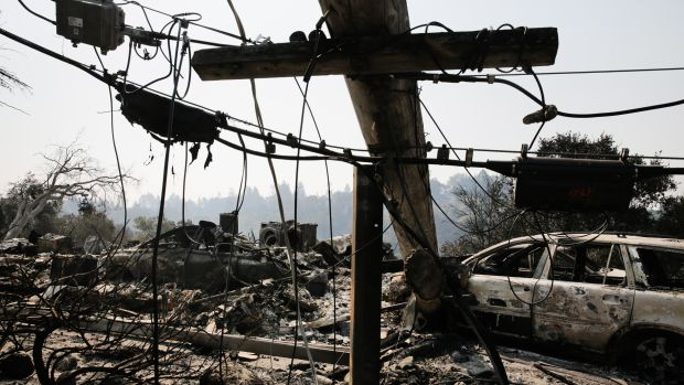 A downed power line and the remains of a home and a car are seen in the Larkfield-Wikiup neighborhood following the damage caused by the Tubbs Fire on October 13th, 2017, in Santa Rosa, California.