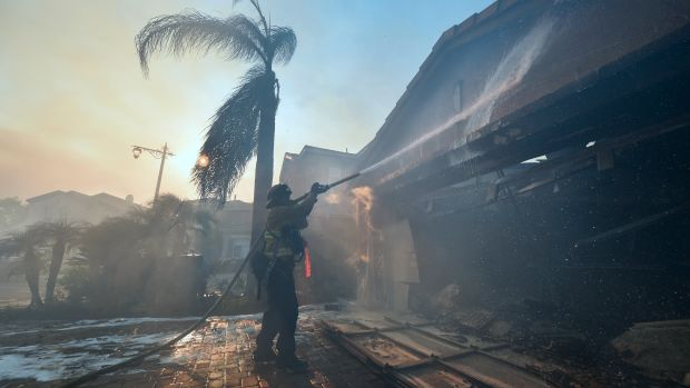 A fireman puts out a fire at a home in the Anaheim Hills neighborhood in Anaheim, California, on October 9th, 2017.