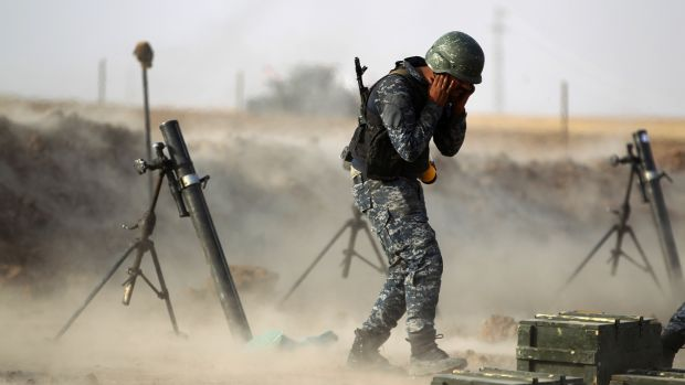A member of the Iraqi forces covers his ears as he fires a mortar against Kurdish Peshmerga positions near the Turkish and Syrian borders in the Iraqi Kurdish autonomous region on October 26th, 2017.