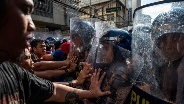 Protesters clash with riot police as they march in the streets of Manila on the day of President Donald Trump's arrival on November 12th, 2017, in Manila, Philippines.
