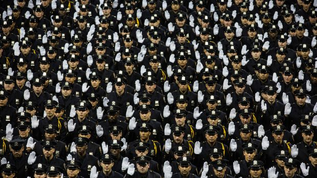 The 2014 class of the New York Police Department raise their hands while taking an oath on June 30th, 2014, at Madison Square Garden in New York City.