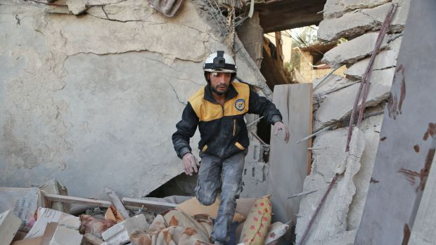 A volunteer from the Syrian Civil Defence searches the rubble of a building following a reported airstrike in the rebel-controlled town of Hamouria on the outskirts of Damascus on November 28th, 2017.