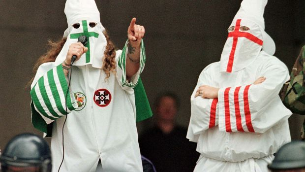 The Grand Dragon of the Michigan Ku Klux Klan (left) addresses the crowd as another Klan member looks on during a rally on August 21st, 1999, in Cleveland, Ohio.