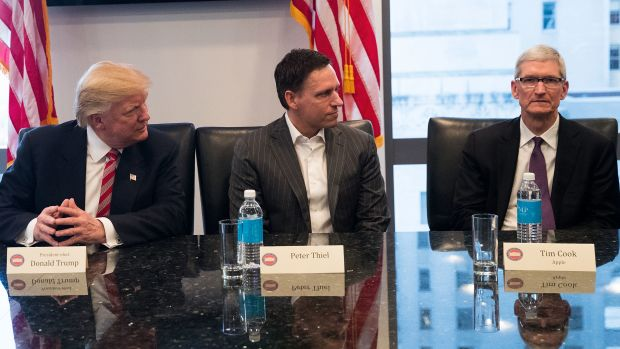 A photo of Donald Trump, Peter Thiel, and Tim Cook.