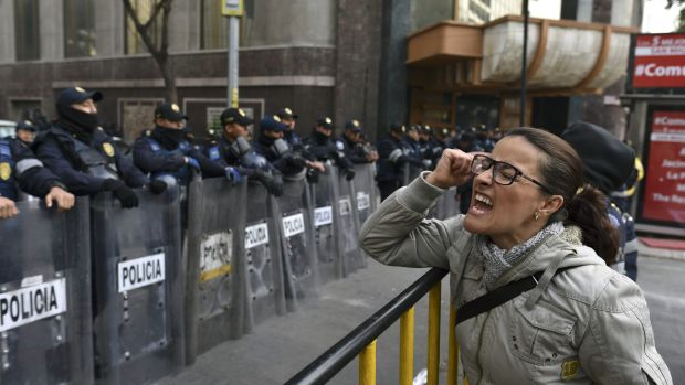 A demonstrator shouts slogans in front of the Senate building during a protest against the potential approval of an internal security law that would allow the army to act as police, in Mexico City, on December 14th, 2017. Mexican deputies approved a new security law that provides a legal framework for military deployment. The controversial initiative is being discussed in the Senate.