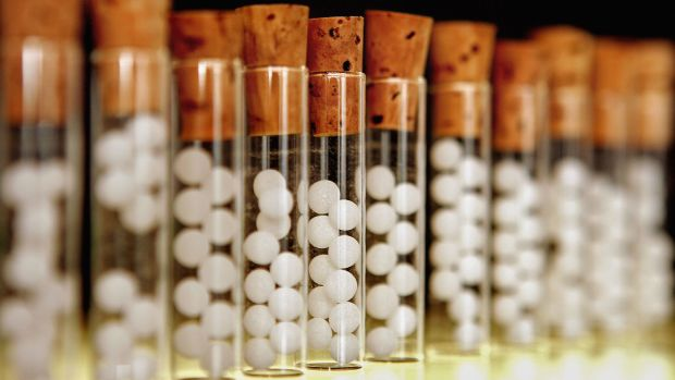 Vials containing pills for homeopathic remedies are displayed at a pharmacy.