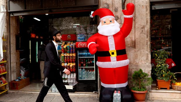 An orthodox Jewish Israeli walks past an inflatable figure of Santa Claus in the Christian Quarter of Jerusalem on December 20th, 2017.