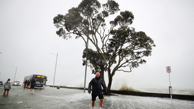 A man walks in the middle of a flooded waterfront on January 5th, 2018, in Auckland, New Zealand. Heavy wind and rain have struck the region, with over 12,000 homes in and around Auckland losing power overnight. More flooding and damage is expected today from continued high winds.