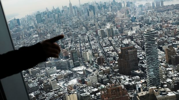 Visitors to the One World Observatory look out at a snow covered Manhattan on January 8th, 2018, in New York City.