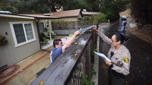 A Los Angeles County sheriff's deputy alerts a resident of mandatory evacuations on January 8th, 2018, in the Creek Fire burn area.
