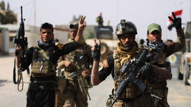 Iraqi forces are seen flashing the sign for victory on November 4th, 2017, in the center of the city of al-Qaim.