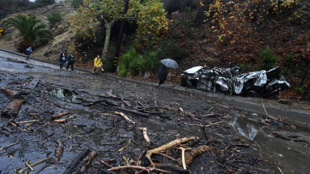 A firefighter instructs journalists to retreat to safer ground after a rain-driven mudslide destroyed two cars and damaged property in a neighborhood under mandatory evacuation in Burbank, California, January 9th, 2018.