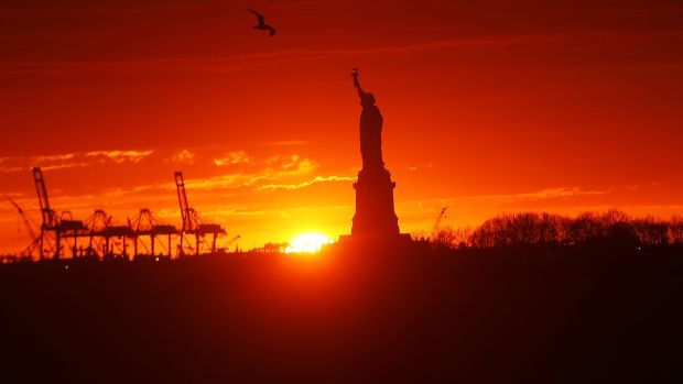 The Statue of Liberty stands in New York Harbor at sunset on January 23rd, 2018, in New York City.
