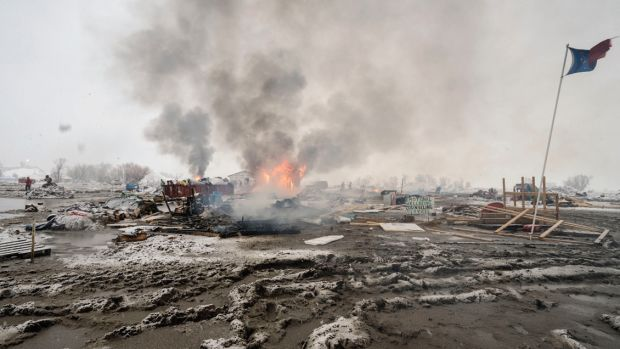 Activists departing the Dakota Access Pipeline protests burn their tents. Next month, we return to Standing Rock one year after the demonstrations.