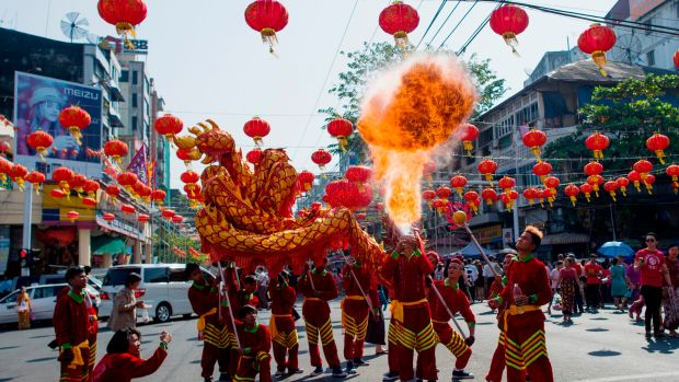 A fire breather blows flames in a traditional dragon dance on the first day of the Lunar New Year in the Chinatown district of Yangon, Myanmar, on February 16th, 2018.