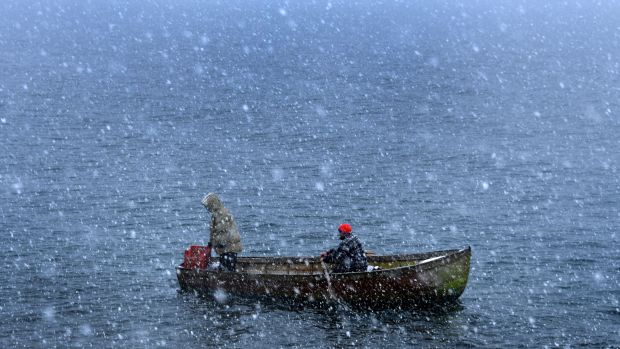 Fishermen row through heavy snowfall as they return to the shores of Lake Ohrid in Pogradec, Albania, on February 27th, 2018. Heavy snow and low temperatures have hit the Balkan countries, including Albania, causing problems for the traffic and power supply.