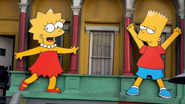 Lisa Simpson and Bart Simpson cut-outs on display at a block party in Los Angeles, California.