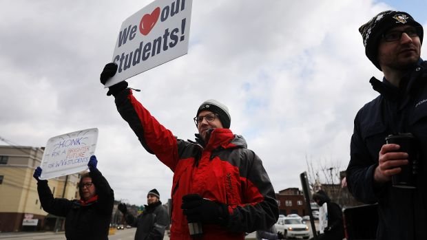 West Virginia teachers hold signs on a Morgantown street as they continue their strike on March 2nd, 2018, in Morgantown, West Virginia.