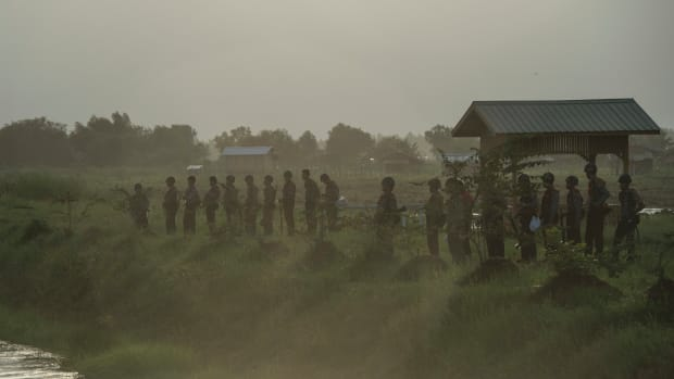 The Myanmar Police Force stand guard by a slum near the outskirts of Yangon on June 12th, 2017.