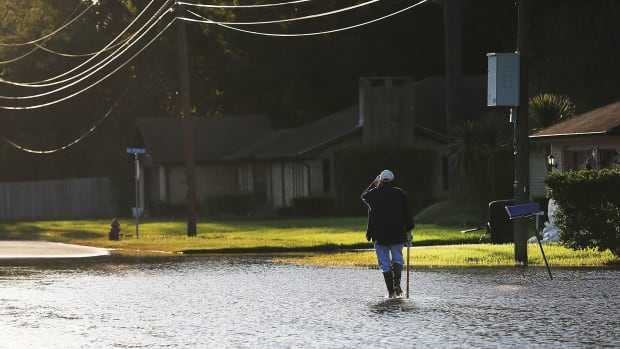 A man walks through his neighborhood in Orange, Texas, on September 7th, 2017.