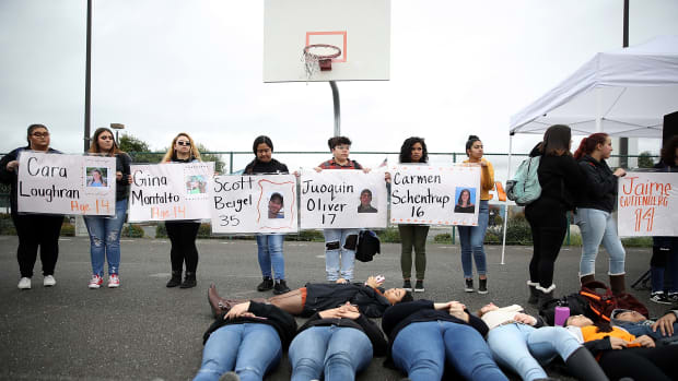 James Logan High School students hold signs honoring students killed at Marjory Stoneman Douglas High School as they observe a moment of silence during a walk out demonstration in Union City, California.