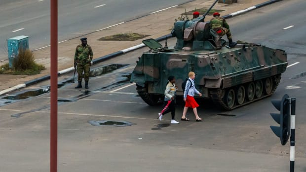 Pedestrians pass a tank stationed at an intersection as Zimbabwean soldiers regulate traffic in Harare on November 15th, 2017. Zimbabwe's military placed President Robert Mugabe under house arrest and took control of the country in an apparent coup on Wednesday.