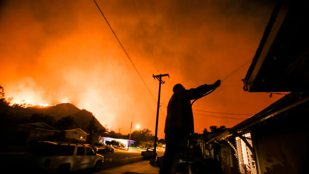 A man waters his home as firefighters battle the Thomas fire along a hillside near homes in Santa Paula, California, on December 5th, 2017.