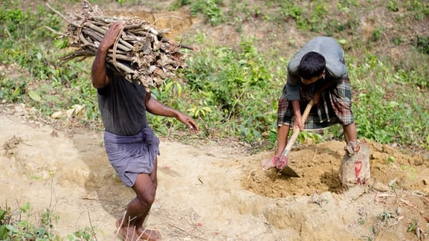 A Rohingya boy chopping wood from a tree stump he freed from soil near Kutupalong-Balukhali refugee camp in Bangladesh.