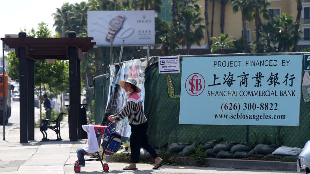 A woman pushes a stroller in San Gabriel, California, on May 17th, 2016, past a banner at a construction site project financed by the Shanghai Commercial Bank.