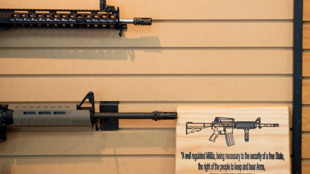 A placard about gun rights hangs on the wall next to assault rifles for sale at Blue Ridge Arsenal in Chantilly, Virginia, on October 6th, 2017.