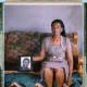 """A posed portrait of Boniwe Tyatyeka, mother of a lesbian named Nontsikelelo Tyatyeka (in the framed picture), who disappeared on September 7th, 2010.""""I am Boniwe, mother of Nontsikelelo Tyatyeka. It is difficult to move forward and continue after losing Ntsikie because she was a girl who made my life happy. She loved to say jokes, make people laugh, write, and dance. If she was upset, she would make jokes and make me laugh. Sometimes when I did something bad and [she] saw that I was upset, I would leave. When I returned from my work the next day, I found a message from Ntsikie stuck in the refrigerator or by my bed where she told me how she felt and apologized. For my Nontsikelelo was different from her sisters and so it will always remain in my heart. Still today when I go out, I look out in the hope of finding Ntsikie. Ntsikie was a girl with dreams.""""(Photo: Robin Hammond/NOOR)"""