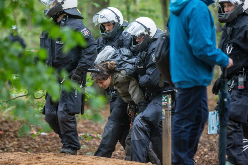Policemen lead an environmental activist off the Hambach Forest on September 13th, 2018.