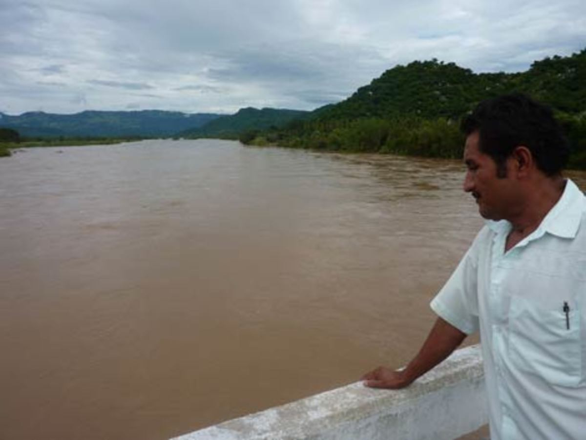 Hilario, coordinator of Ecosta\'s programs, looking at the Rio Verde. Upstream is Paso de la Reina, one of the many communities to be flooded if the dam is built. (Kristian Beadle)