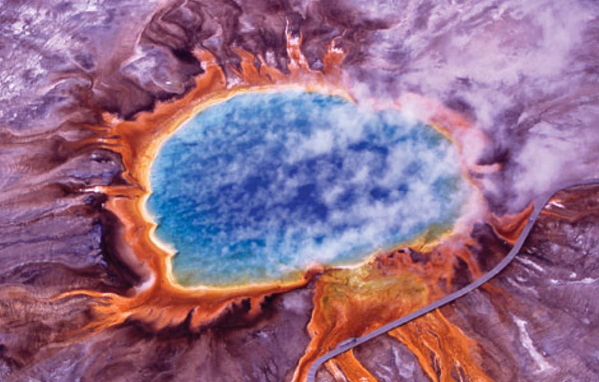 An aerial view of Grand Prismatic Spring in Yellowstone National Park. This hot spring is about 250 by 300 feet. The photo shows steam rising from blue water, surrounded by huge mats of brilliant orange algae and bacteria. (wikimedia)