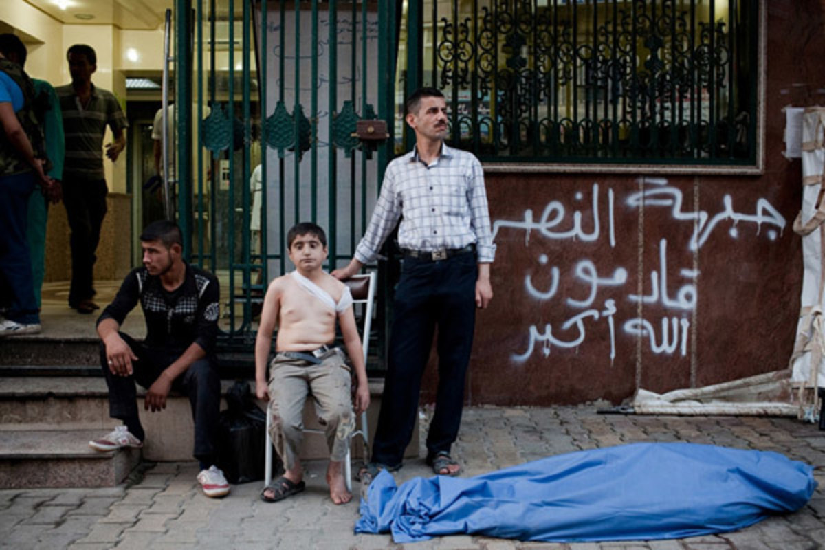A Syrian boy waits with his uncle, right, near the body of his father, who was killed by a shell in Sha'ar. (PHOTO: NICOLE TUNG/SYRIA DEEPLY)