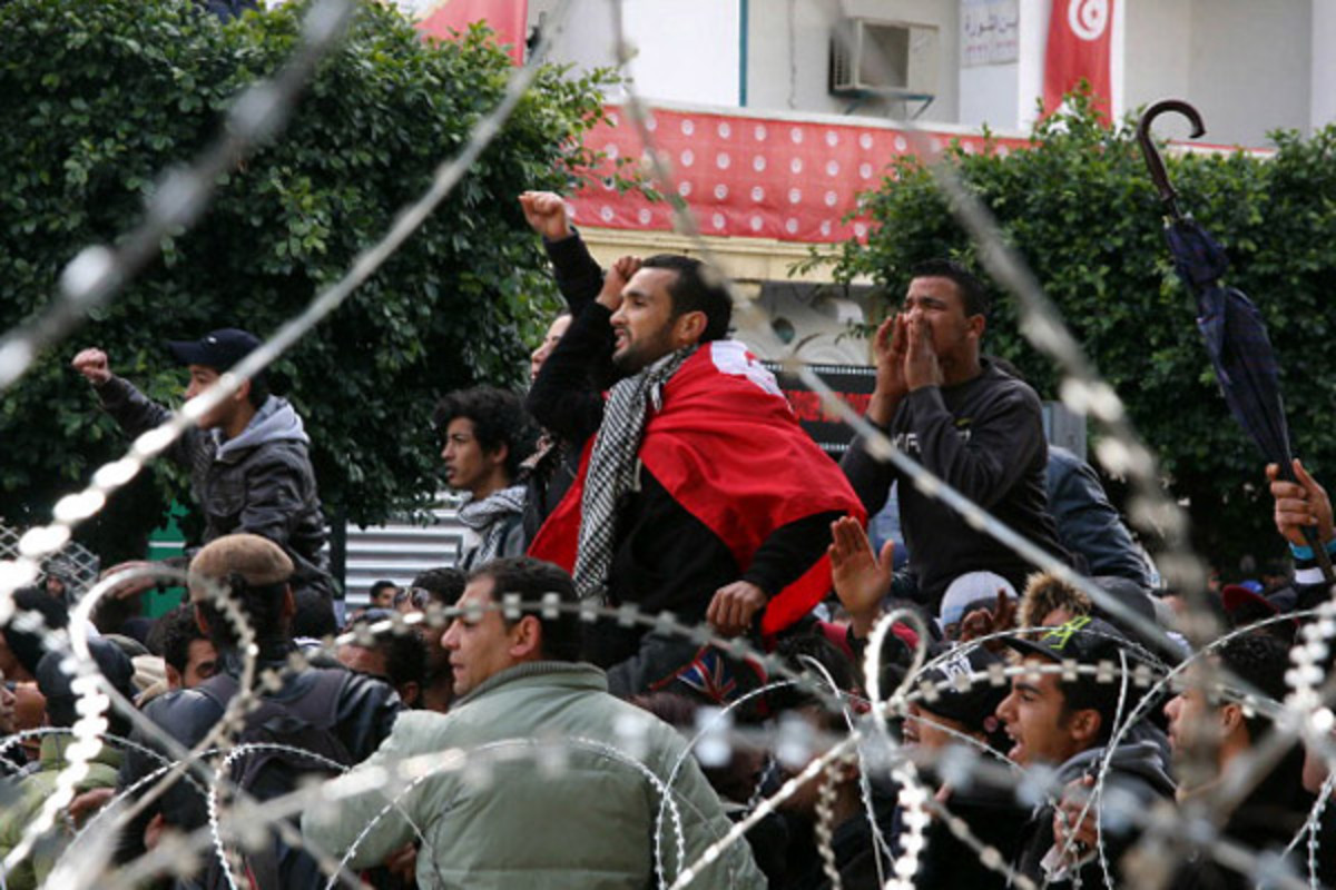 Tunisian protestors chant slogans behind barbed wire outside the Interior Ministry in Tunis, on February 7, 2013 during a demonstration against the killing of opposition figure and human rights lawyer Chokri Belaid. (Photo: KHALIL/AFP/Getty Images)