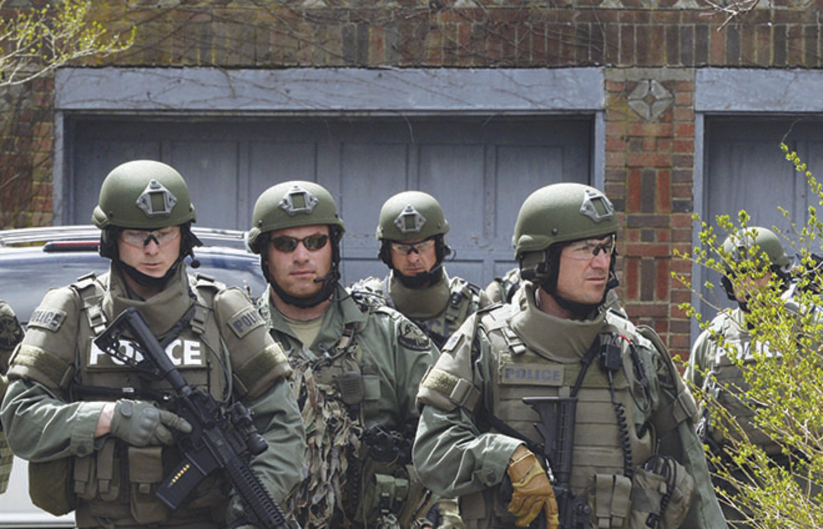 SWAT officers from the Cape Cod Police Department patrol the streets of Watertown. Nationwide, paramilitary police units conduct more than 100 raids a day. (Photo: Timothy A. Clark/AFP)