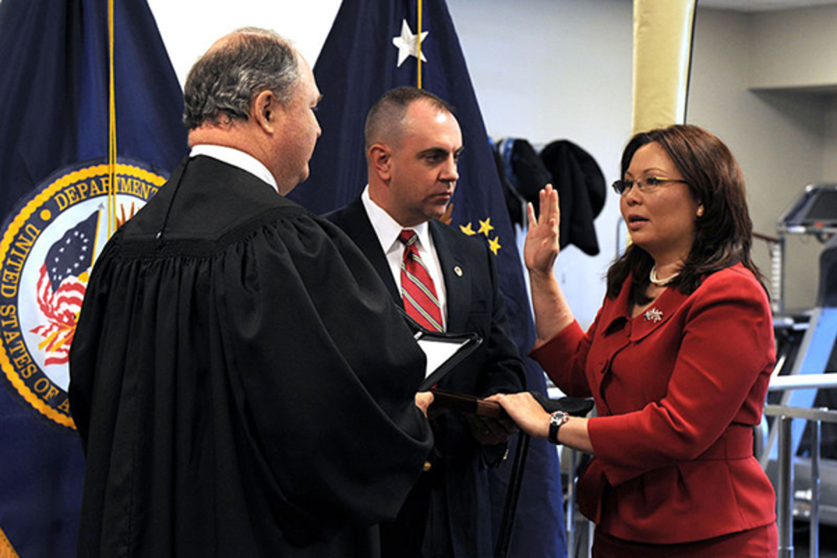 Duckworth being sworn in as Assistant Secretary of Public and Intergovernmental Affairs for the United States Department of Veterans Affairs, by Judge John J. Farley with her husband Bryan Bowlsbey beside her. (PHOTO: PUBLIC DOMAIN)
