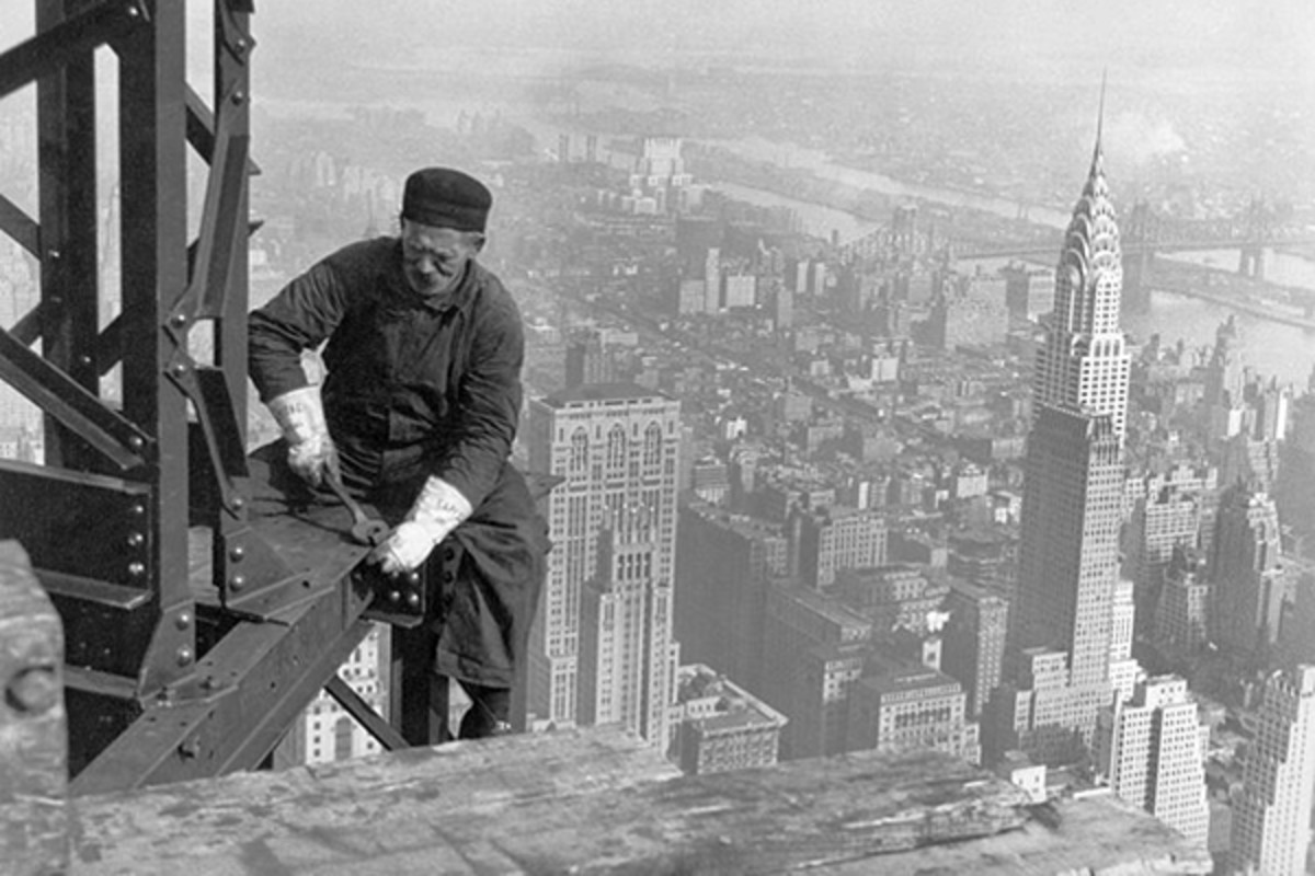 A construction worker on top of the Empire State Building as it was being built in 1930. The Chrysler Building is below and behind him. (PHOTO: PUBLIC DOMAIN)