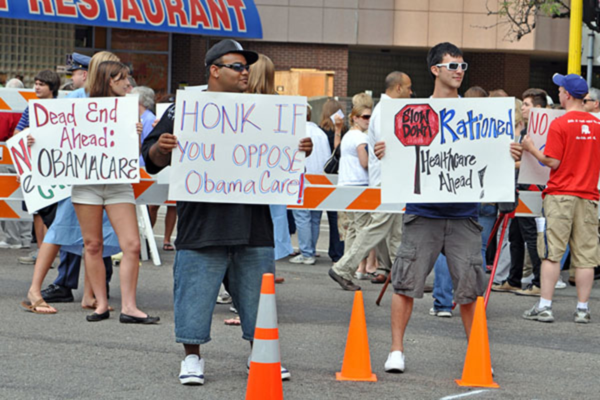 Protesters hold placards outside of Barack Obama's Health Care speech at the Target Center on September 12, 2009, in Minneapolis. (PHOTO: MIKER/SHUTTERSTOCK)