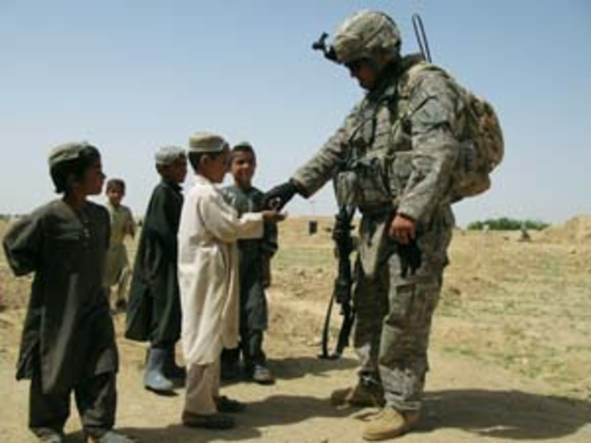 A U.S. soldier passes out candy in Pir Zadeh in southern Afghanistan. (Vanessa M. Gezari)