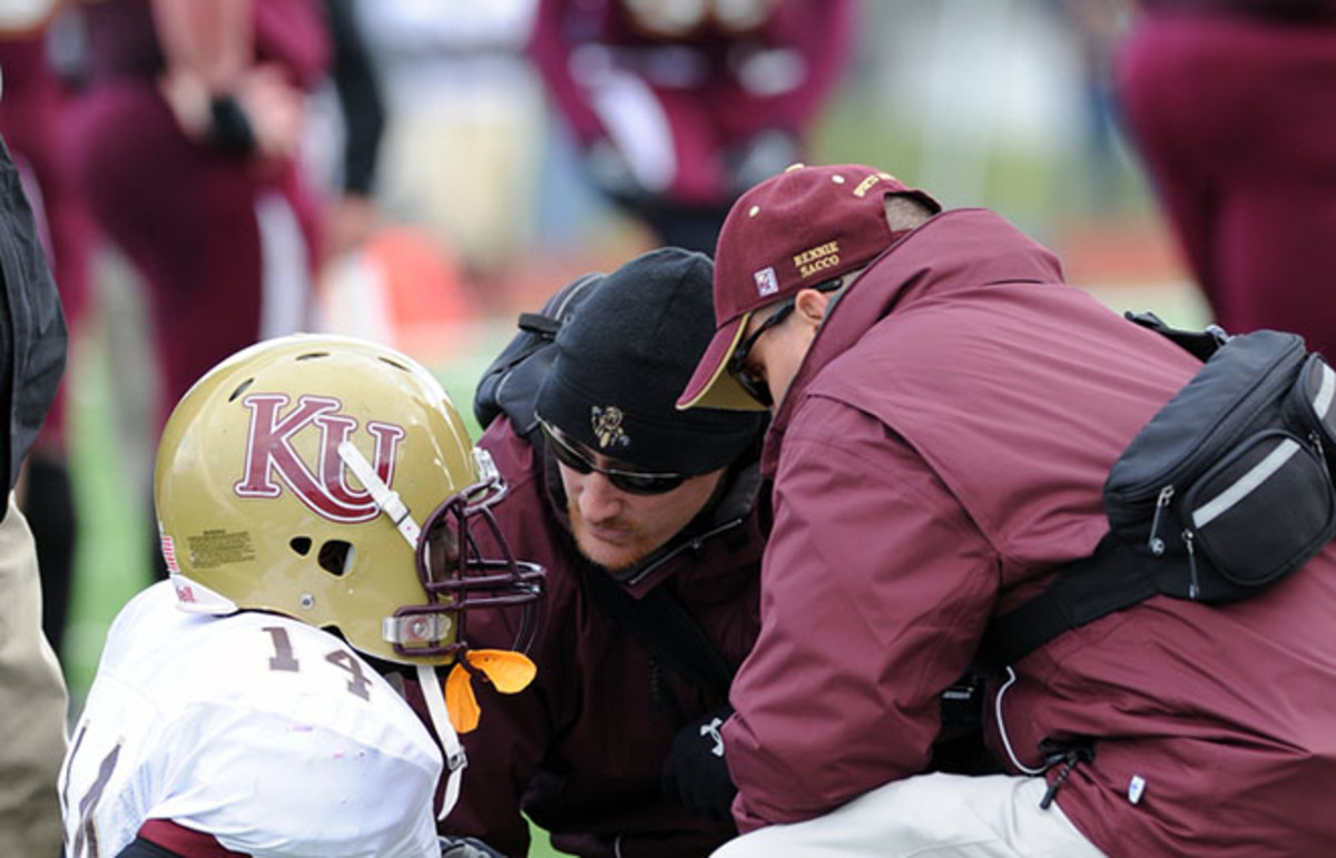 Kutztown University defensive back Corey Harris is checked out on the field by training staff after an injury in a game. (Photo: Aspen Photo/Shutterstock)