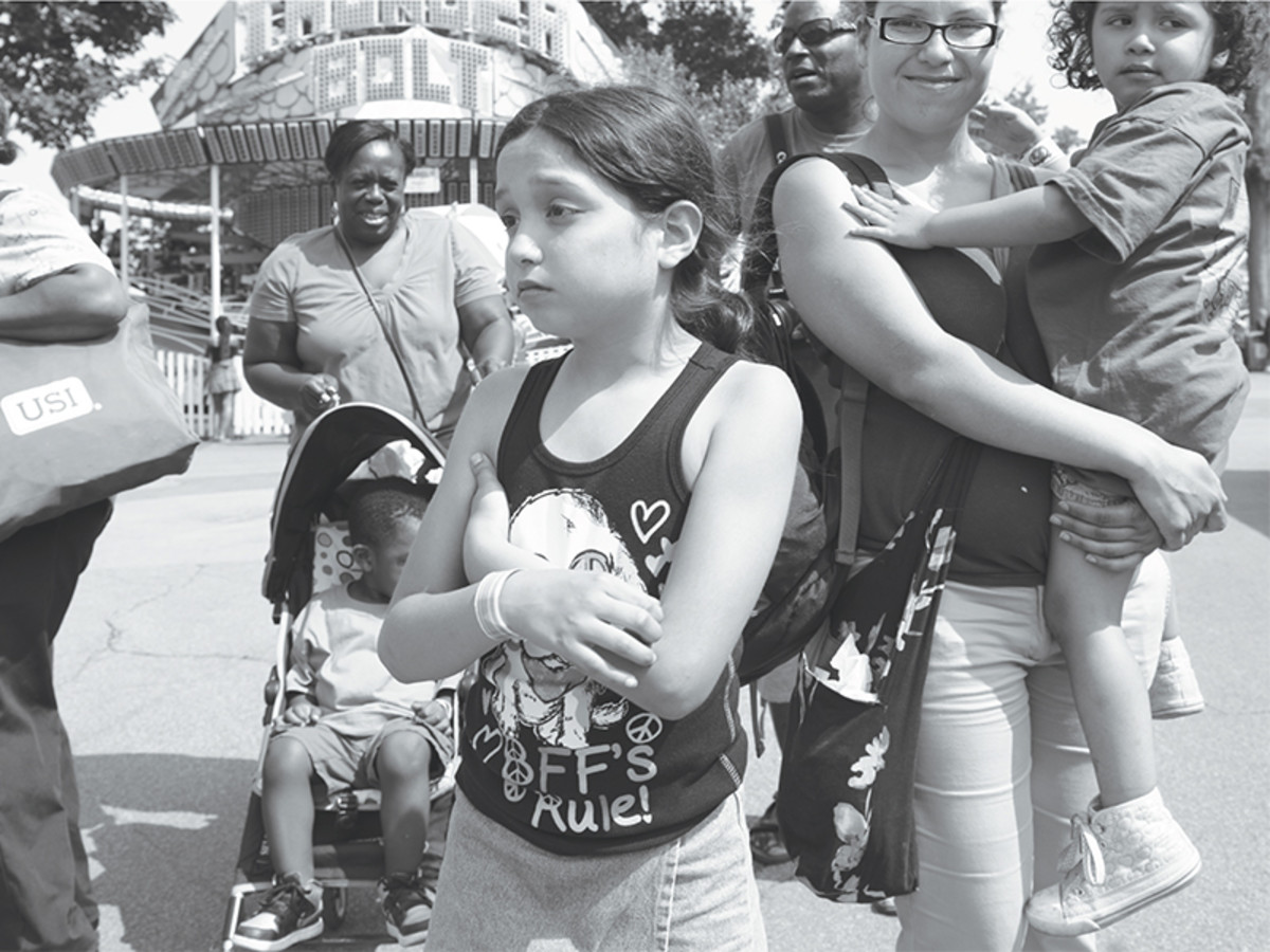 Dee's Tots organizes field trips, such as this one to a nearby amusement park. Eight-year-old Diana was unhappy because her mother (holding her four-year-old daughter, Ivette) had to end the outing and leave for work.