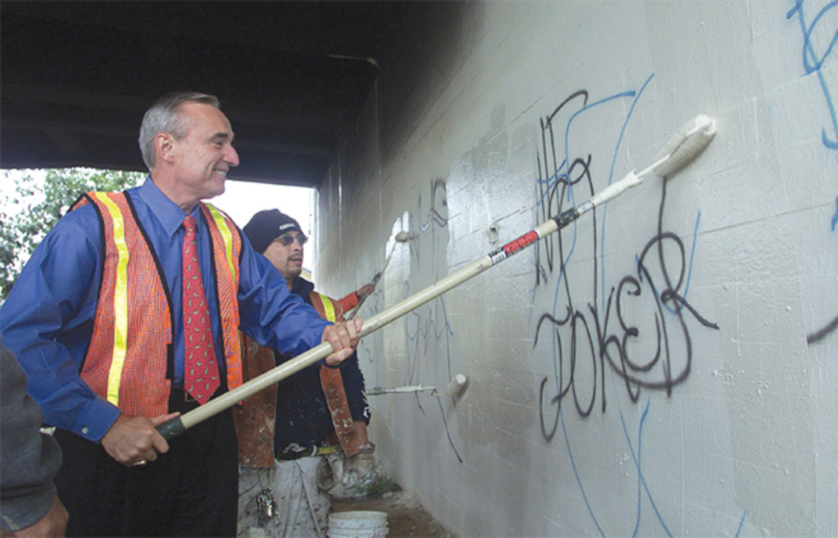 PAINTING BY NUMBERS: Former police chief William Bratton, left, and mayor Jim Hahn (not pictured) painted walls in the Boyle Heights area to kick off their fight against graffiti. (Photo: Jean Marc Bouju/AP)
