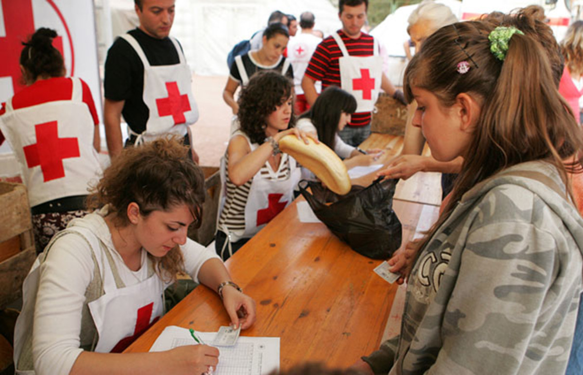 Red Cross workers distribute food at a refugee camp on September 8, 2008, in Gori, Georgia. (Photo: kojoku/Shutterstock)