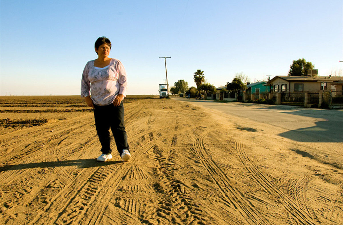Teresa DeAnda, an environmental justice advocate, stands on the dirt  road between an agricultural field and her neighborhood. (Photo: Voices From the Valley)