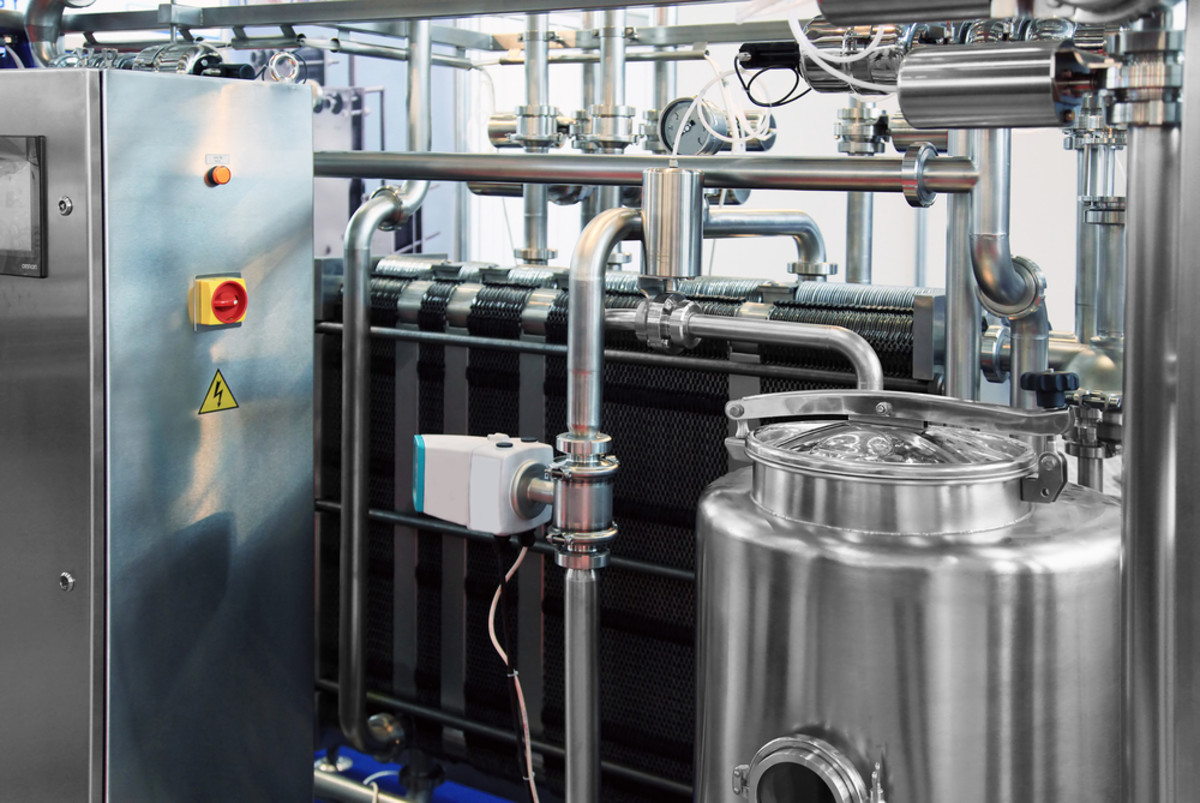 Dairy factory with milk pasteurization tank and pipes. (Photo: sspopov/Shutterstock)
