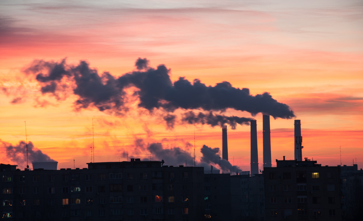Coal power plant emissions seen above residential blocks from a city during sunrise. (Photo: ldphotoro/Shutterstock)